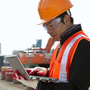 Construction worker with hard hat checking his laptop